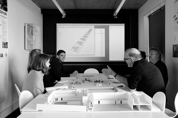 Design Engine Our philosophy image directors at architects discussing a project around a model